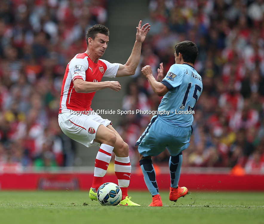 13 September 2014 , Premier League ,  Football Arsenal v Manchester City - Laurent Koscielny of Arsenal wins the ball in a tackle with Jesus Navas<br /> Photo: Mark Leech .