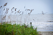 A shrimp boat works the trawls the coastline at Isle of Palms, SC