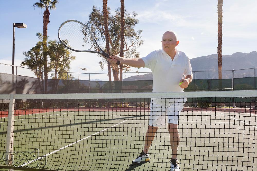 Senior male tennis player preparing to serve on court