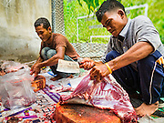 12 SEPTEMBER 2016 - BANGKOK, THAILAND:   Men butcher freshly sacrificed goats during the Qurbani (ritual sacrifice of livestock) at the celebration of Eid al-Adha at Haroon Mosque in Bangkok. Eid al-Adha is also called the Feast of Sacrifice, the Greater Eid or Baqar-Eid. It is the second of two religious holidays celebrated by Muslims worldwide each year. It honors the willingness of Abraham to sacrifice his son, as an act of submission to God's command. Goats, sheep and cows are sacrificed in a ritualistic manner after services in the mosque. The meat from the sacrificed animal is supposed to be divided into three parts. The family retains one third of the share; another third is given to relatives, friends and neighbors; and the remaining third is given to the poor and needy.        PHOTO BY JACK KURTZ