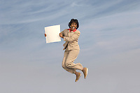 Business woman jumping with blank sign outdoors