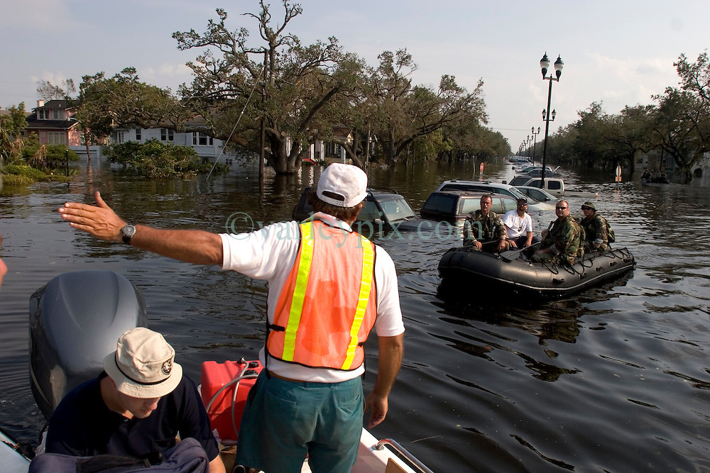 05 Sept  2005. New Orleans, Louisiana. Post hurricane Katrina.<br /> Animal rescue boat. Local man Jimmy Delery gives directions to soldiers bobbing in the devastating floods in Uptown New Orleans.<br /> Photo; &copy;Charlie Varley/varleypix.com