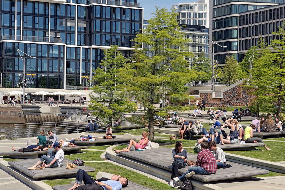 Leute bei der Mittagspause in der Sonne an den Marco-Polo-Terassen in der Hafencity Hamburg.