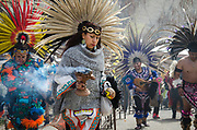 Traditional Aztec dancers enter the courtyard at El Santuario de Chimayo during Easter weekend. Griselda Garcia leads the procession, the company of dancers hails from Mexico City.