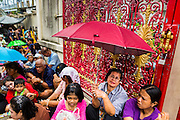 """09 AUGUST 2014 - BANGKOK, THAILAND:      People sit under umbrellas while they wait for a food distribution to start at the Ruby Goddess Shrine in the Dusit section of Bangkok. The seventh month of the Chinese Lunar calendar is called """"Ghost Month"""" during which ghosts and spirits, including those of the deceased ancestors, come out from the lower realm. It is common for Chinese people to make merit during the month by burning """"hell money"""" and presenting food to the ghosts. At Chinese temples in Thailand, it is also customary to give food to the poorer people in the community.    PHOTO BY JACK KURTZ"""