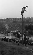 Boy climbing on lamp post, High Wycombe, UK, 1980s.