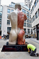 "© Licensed to London News Pictures. 24/06/2017. London, UK. A workman polishes the plinth of a 21 feet tall, 2.5 tonne bronze sculpture called ""Temple"" by Damien Hirst that has been unveiled near the Lloyds Building in the City of London.  The artwork will be on display as part of ""Sculpture in the City"", a festival of sculpture in the City of London showing works by leading artists. Photo credit : Stephen Chung/LNP"