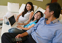 Family Relaxing on sofa in Living Room daughter with Laptop