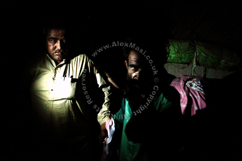 A kidnap suspect (right) is being detained for questioning by a member of the AVCC, (Anti-Violence Crime Cell) a special police unit mostly involved in anti-terrorism operations and kidnap cases in the city of Karachi, Pakistan's main economic hub.