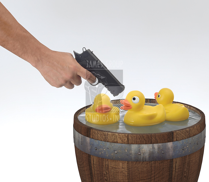 Arm of a person holding a pistol and shooting rubber ducks in a barrel