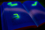 Glowing bookworms crawling over and eating through an old book.Black light