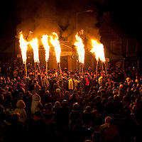 Comrie Flambeaux, Perthshire.....Each Hogmanay as midnight is announced by the bells of Big Ben the flambeaux are lit. The torches which consist of long thick birch poles with tarred rags bound to the tops arae paraded around the village of Comrie in Perthshire preceeded by a pipe band. The centuries old tradition is supposed to signify the casting out of evil spirits...The pictured shows the flambeaux procession making its way through Melville Square in Comrie.<br /> Picture by Graeme Hart.<br /> Copyright Perthshire Picture Agency