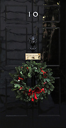© Licensed to London News Pictures. 07/12/2011, London, UK. A Christmas wreath hangs on the door at Ten Downing Street today 7th December 2011.  Photo credit : Stephen Simpson/LNP