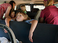 Hannah Jeub, 6, hangs over the seat as her family loads into their 15 passenger van with every seat taken in Monument, Colorado July 17, 2009.  Quiverfull believers Wendy and Chris Jeub have 15 children and would be happy to have more if God wills it they say. Picture taken July 17, 2009. REUTERS/Rick Wilking (UNITED STATES SOCIETY RELIGION)