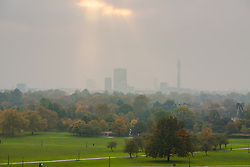 Primrose Hill, London, October 30th. The sun begins to break through as mist shrouds London's skyline, as dog walkers and fitness fanatics enjoy Primrose Hill. Pictured: The sun breaks through bathing London in soft, diffused light.
