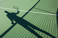 Shadow of senior man playing tennis on court