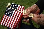 Free American flags were passed out before the 85th Annual Memorial Day services at Veterans Memorial Cemetery at Evergreen Washelli. <br /> Greg Gilbert/The Seattle Times