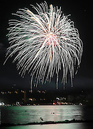 Beacon, New York -  Independence Day fireworks explode in the sky over Newburgh and reflected in the Hudson River as seen from a waterfront park on July 4, 2010. A bird with a fish is visible on the rocks in the lower part of the image.