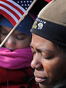 Tears trickle down the cheek of Bridgette Wright of Dacula, Georgia,.as her daughter, Leah holds an American flag during the opening prayer.of the inauguration of Barack Obama..