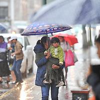 Toluca, México.- Aspectos generales de la lluvia que cayó esta tarde en el centro de la ciudad de Toluca, personas con paraguas caminan sobre los charcos de agua. Agencia MVT / Mario Vázquez de la Torre.
