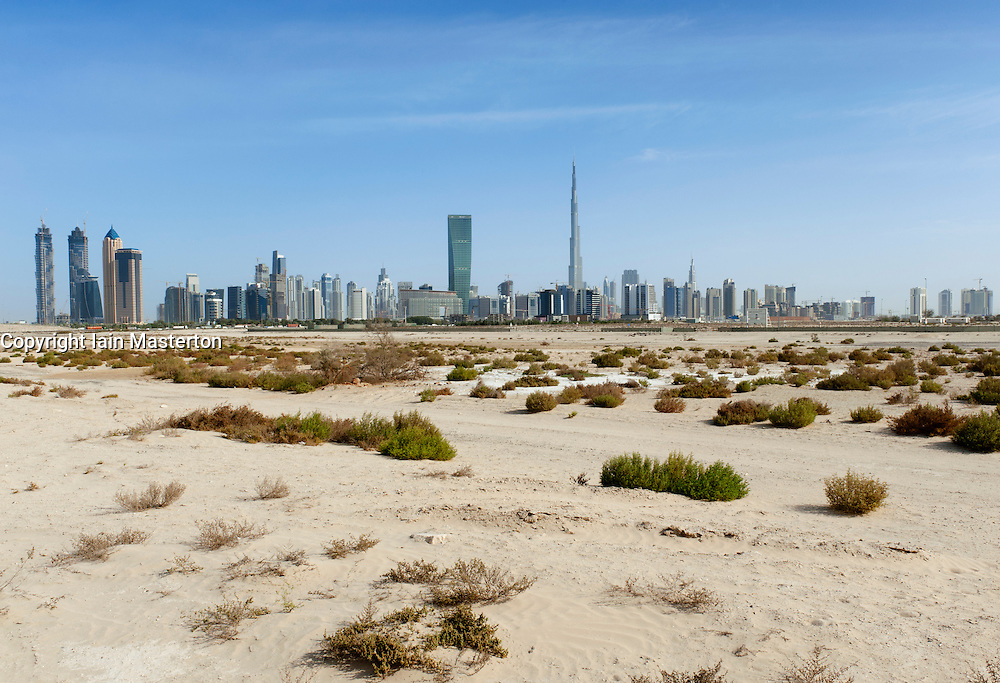 Skyline of Dubai with Burj Khalifa tower prominent and desert in foreground in United Arab Emirates , UAE