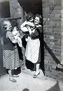 mother and grandmother holding toddler and baby 1940s England