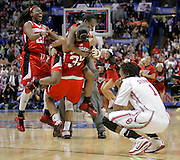 As the final buzzer sounds, Louisville players celebrate their 61-59 win as Oklahoma's Nyeshia Stevenson sinks to her knees after missing a three point shot which would have won the game in their NCAA Final Four semi-final game in St. Louis, MO.