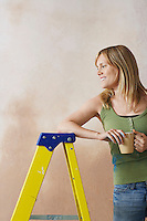Smiling woman leaning on step ladder holding mug