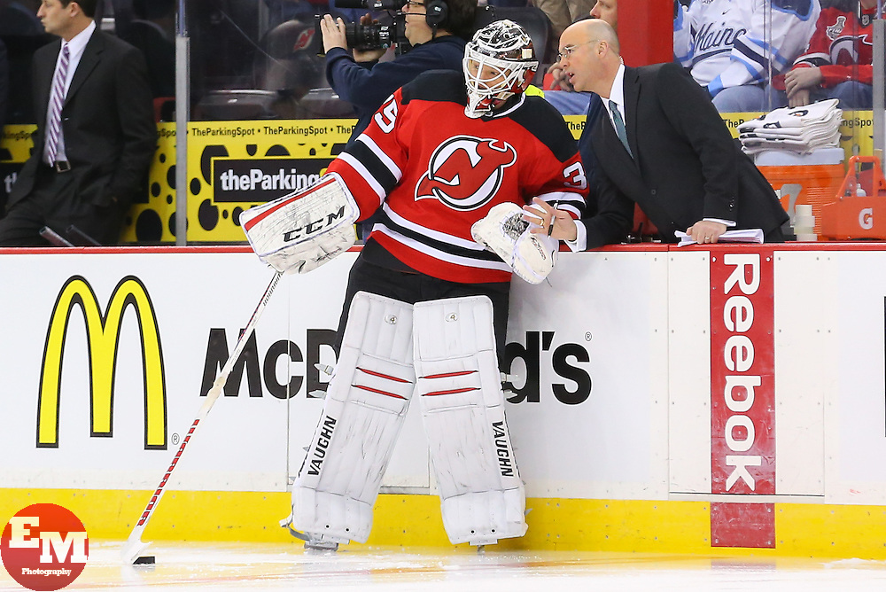 Mar 31, 2014; Newark, NJ, USA; New Jersey Devils goalie Cory Schneider (35) speaks with NBC's Pierre McGuire during the pre game warmups for their game against the Florida Panthers at Prudential Center.
