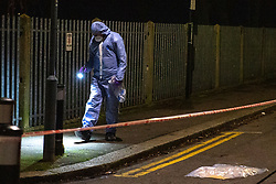 © Licensed to London News Pictures. 20/01/2020. London, UK. A forensic investigator searches for evidence next to an evidence bag covering an unknown item. Police cordoned off a road & park and searched a property approximately half a mile from the location where an investigation was launched into the deaths of three men in Redbridge, all of whom had suffered apparent stab injuries.. Photo credit: Peter Manning/LNP