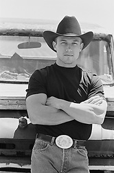 Man in a Cowboy hat and large belt buckle leaning against a truck