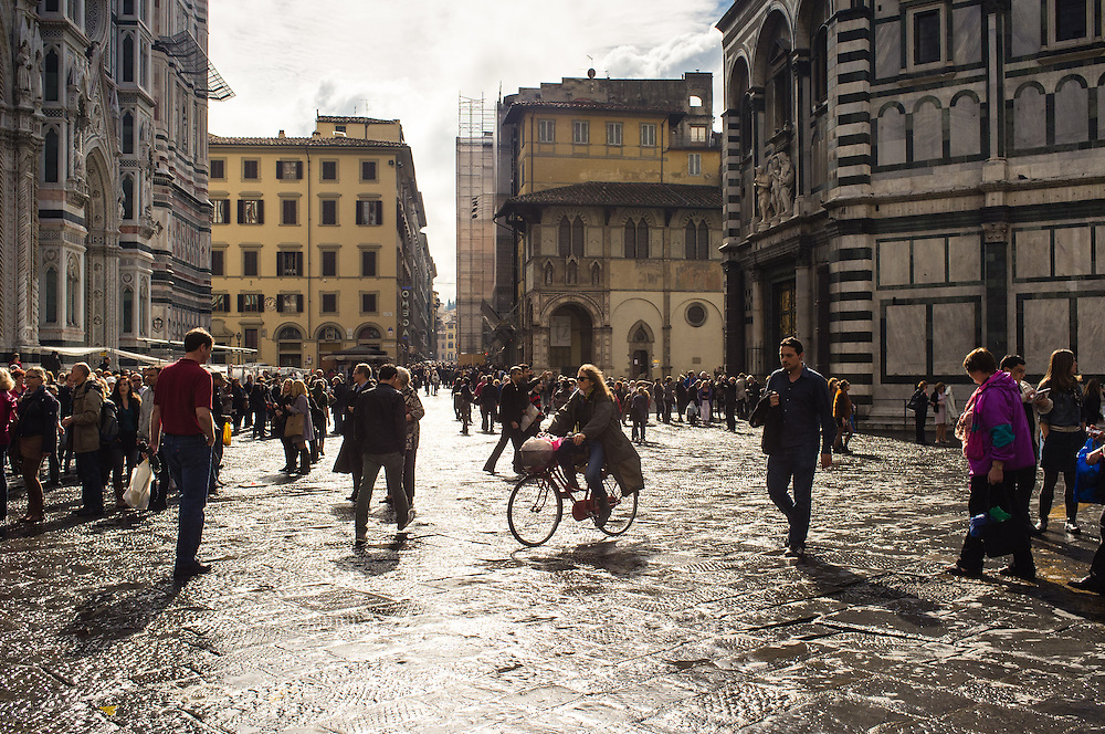 Crowds of tourists walking and on bikes in Florence, Italy