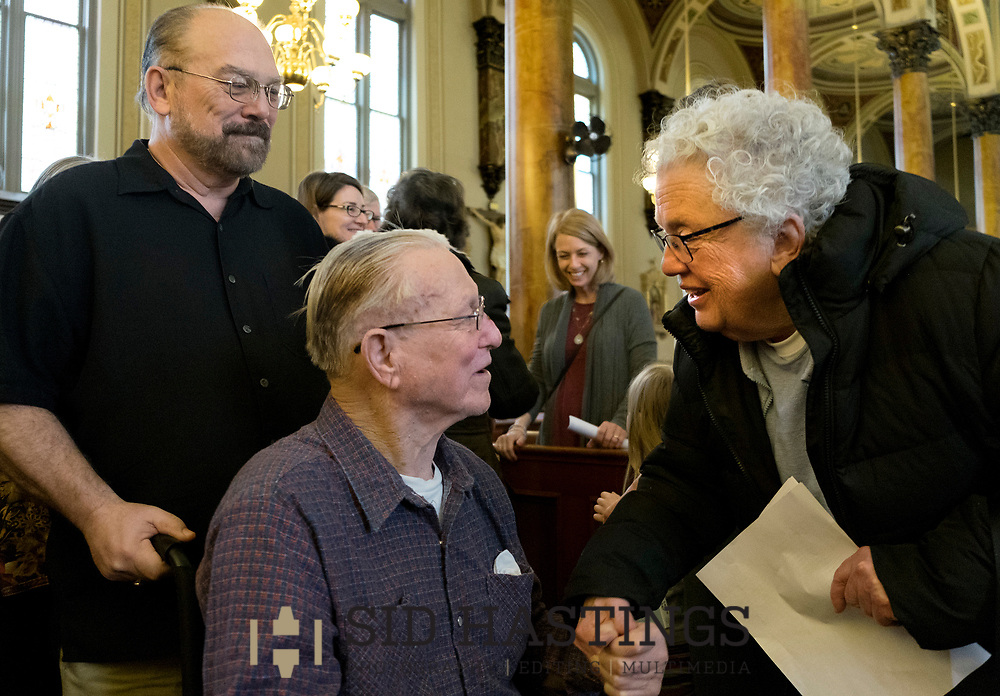 11 MARCH 2018 -- ST. LOUIS -- Francis Aubuchon (center), a descendant of German immigrant Ignatius Strecker, greets Jane Rhoda while being assisted by his son Mark Aubuchon (left) after Mass at the Shrine of St. Joseph Sunday, March 11, 2018 in the Columbus Square neighborhood of St. Louis. Aubuchon and other Strecker descendants gathered to remember the healing of the Strecker, thought mortally ill, during an 1864 service honoring Jesuit priest Peter Claver, a missionary who worked among slaves in South America during the 17th century. Strecker's healing was among the miracles attributed to Claver that led to his 1888 canonization by Pope Leo XIII. Photo © copyright 2018 Sid Hastings.
