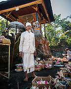 Balinese priest standing among the village's offerings at Pura Luhur Dalem temple, Penebel, Bali
