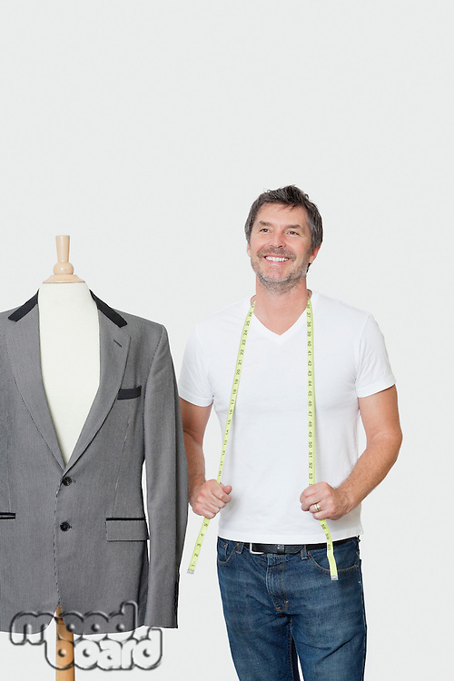 Mature male dressmaker standing next to tailor's dummy over gray background