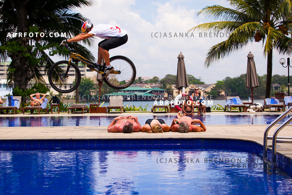 Belgian mountain bike trials cyclist Kenny Belaey completes a jump over tourists relaxing poolside at the Cinnamon Lakeside Hotel.