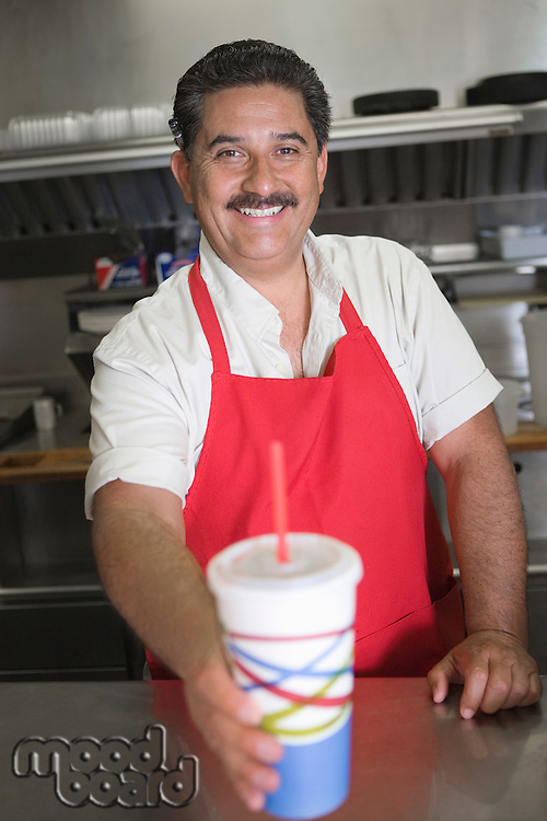 Portrait of man serving drink in restaurant