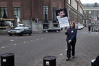 Nederland. Den Haag, 18 februari 2010. <br /> Eenzame demonstrant tegen de Nederlandse aanwezigheid in Uruzgan en tegen het beleid van het kabinet Balkenende Vier. Voor aanvang van het Spoeddebat in de Tweede Kamer over de ontstane crisissituatie binnen het kabinet over Uruzgan, daags voor de val van het vierde kabinet Balkenende. Een dag later valt het kabinet. kabinetscrisis, vak kabinet, Balkenende IV, Balkenende Vier, politiek, coalitie<br />  Foto Martijn Beekman