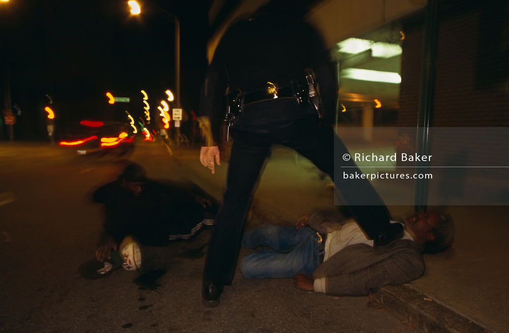 An officer from the Atlanta Police Department puts his boot on a man's chest who is lying still in the gutter on the street. He and another person have been fighting in the downtown area and the officer has arrived in his patrol car after reports that a street brawl needed his interception. The officer's belt with a gun secured in its holster  can be seen from a low ground level angle. It is a desolate and sinister place and the lights from a passing car and the green fluorescent glow from a parking lot (car park) is in the background. The police officer needs to calm the violent situation, pacifying the two men before the matter gets out of hand and preventing him from causing more trouble, he places his weight on the thorax to pin the male on the ground.