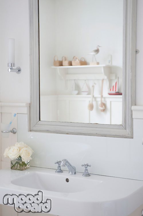 Grey painted mirror surround above washbasin London