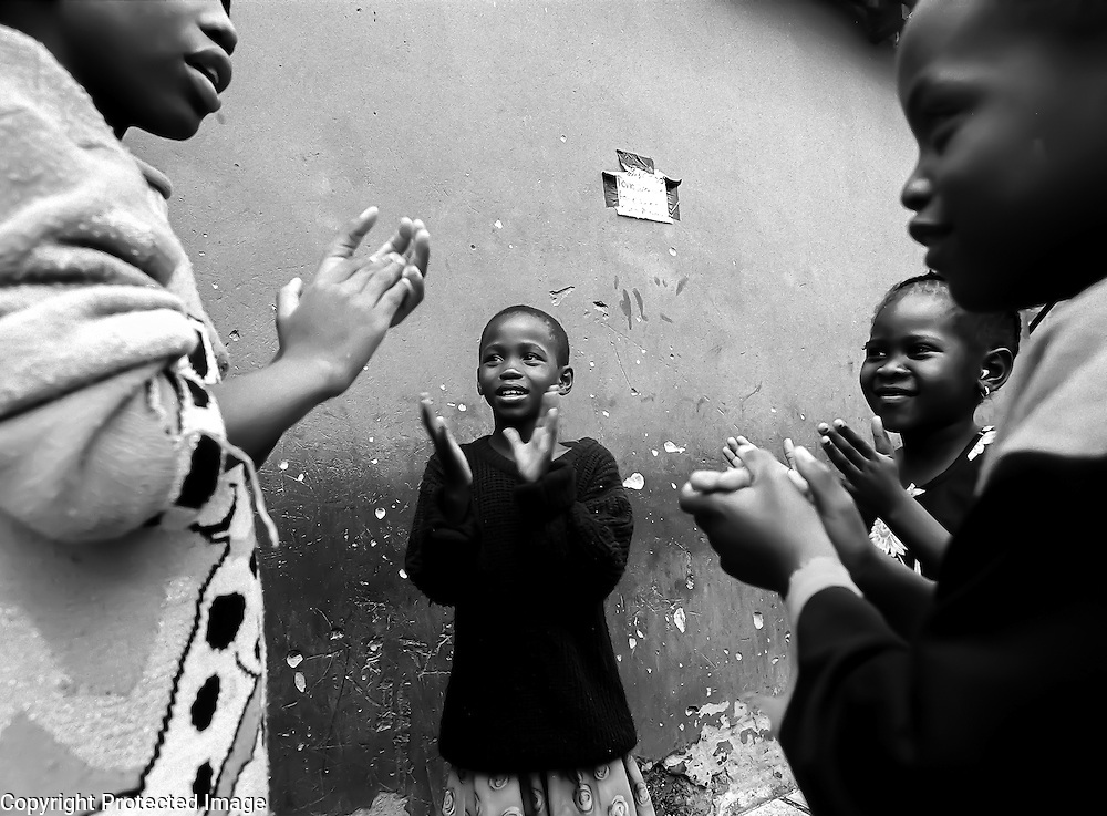 Alona Mthimkhunu (center) plays a clapping game with, at far left, her sister, Patience, 12, and neighborhood children.  Without access to television or other forms of entertainment, Alexandria Township children play clapping, skipping or stone-tossing games.  The township, which is across the highway from one of Johannesburg's wealthiest suburbs, is extremely overpopulated has one of the highest murder rates in the world.