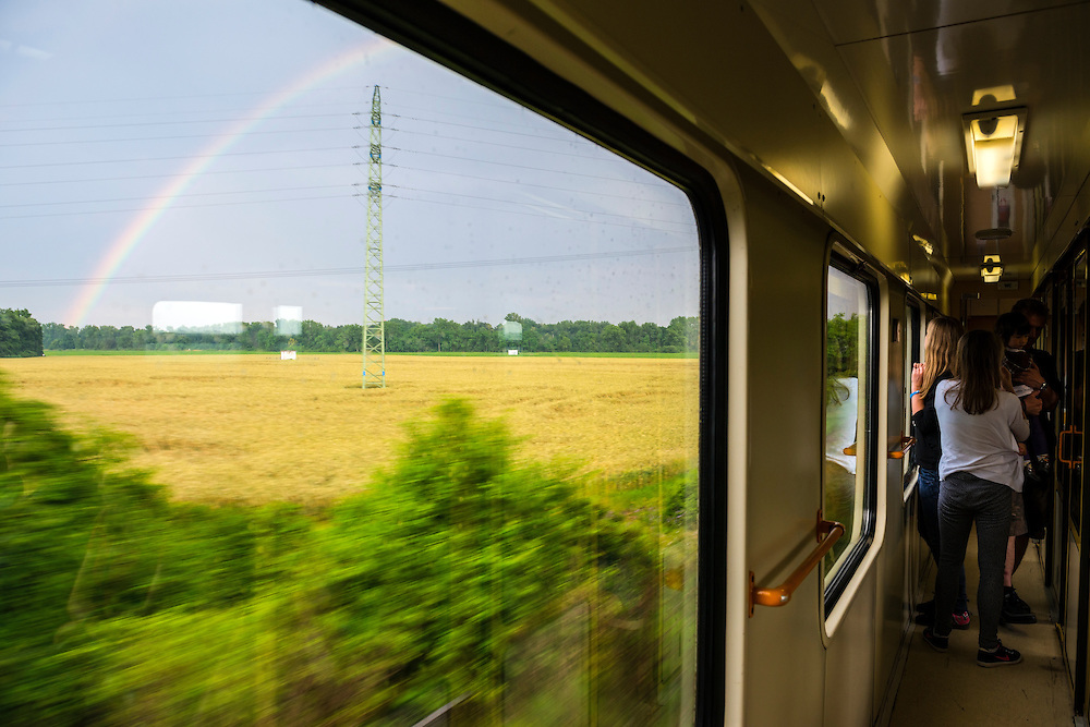 Passengers stand inside a train traveling between the Czech cities of Kutna Hora and Prague. One is looking at the beautiful rainbow outside the window. Time is 7:17pm.