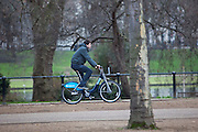 A man on a Barclays cycle hire bike cycling along the Mall with St James Park in the background, London.