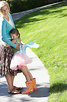 Girl wearing fairy wings and tutu hugging mother in park