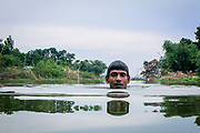 Mohammad Khokon swims in the Jamuna River where his house used to be. A flash flood washed it into the Jamuna River in Sirajganj, Bangladesh in 2007.<br /> Global warming cause the monsoon rain and floods to start earlier. Global warming also accellerate the melting of the ice and snow in the Himalayas, which feeds into the already saturated rivers that make the Ganges Delta. The result is devastating to people who live in the densely populated delta area.<br /> While the Himalayas and flooding wreak havoc from the north, rising sea levels cause salt water intrusion in the low-lying agricultural zones along the coast.<br /> According to the World Bank, coastal Bangladesh can easily see a 15 percent drop in rice production in the coastal regions within year 2050. The Khulna region is already damaged by salt water, but attempts are made to grow different strands of rice that can handle the stress.<br /> One of the poorest countries in the world, Bangladesh is also one of the most vulnerable to climate changes. With a sea level rise of 1.5 meter, close to 17 million people will be affected, according to GRID-Arendal, a knowledge center collaborating with UNEP.