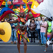 Hackney carnival 2014. The procession started in Ridley Road and passed by the The Hackney Town Hall with thousands of spectators lining the road. A young dancer poses in her colourful costume outside the local Sainsbury's.