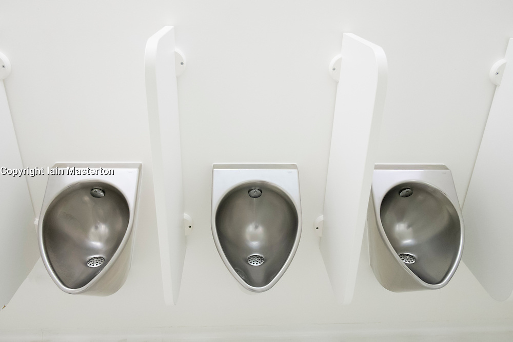 Modern stainless steel urinals in mens lavatory
