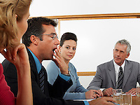 Businessman yawning in conference meeting