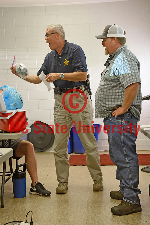 "Rockingham County Sheriff Sam Page (left) reacts to finding ""suspicious"" materials with hemp farmer Calvin Whitfield during a role-playing presentation to law enforcement officers at the Piemont Research Station."