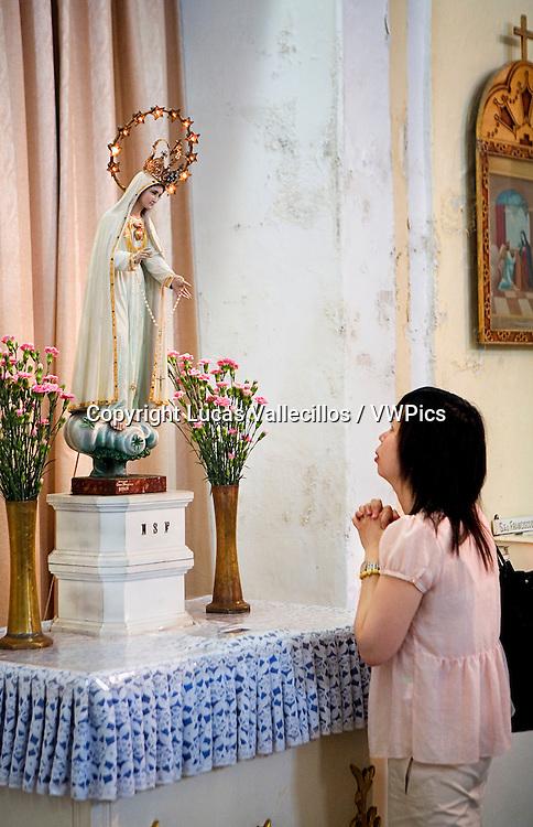 Woman praying, St Dominic´s Church, in St Dominic´s square,Macau,China